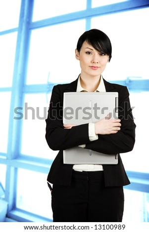 A shot of a beautiful businesswoman carrying a laptop in the office