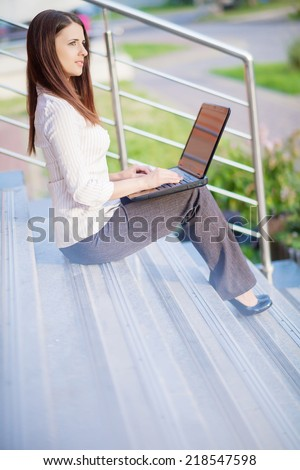 A shot of a beautiful businesswoman working on her laptop outdoor  - stock photo