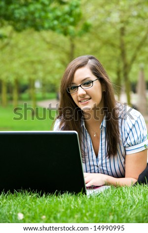 A shot of a beautiful caucasian businesswoman lying down on the grass working on her laptop