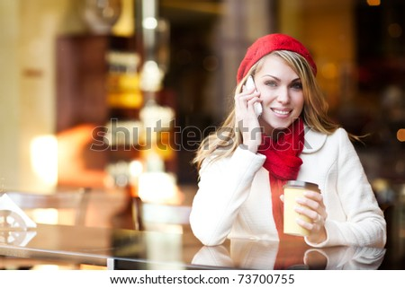 A shot of a beautiful caucasian woman talking on the phone at a cafe - stock photo