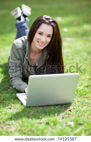 A shot of a beautiful ethnic college student working on her laptop on campus