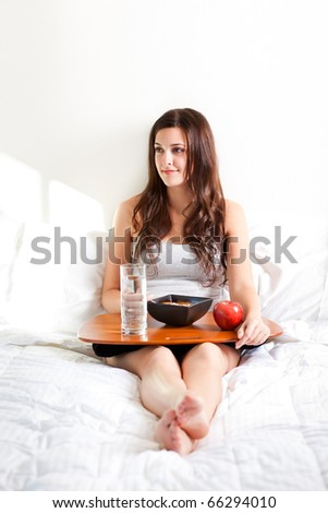 A shot of a beautiful girl eating breakfast in bed