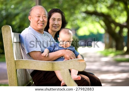 A shot of a cute asian child with his grandparents in a park - stock photo