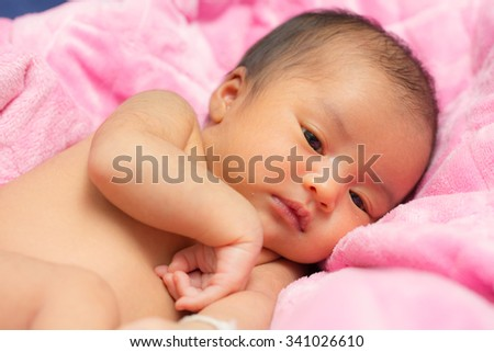 A shot of a cute newborn asian baby 14 days after birth