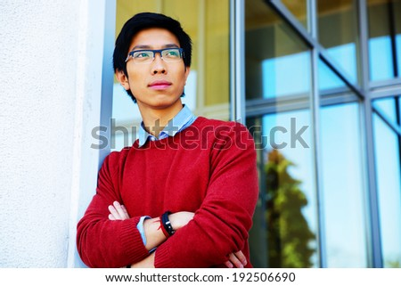 A shot of a handsome young asian student - stock photo