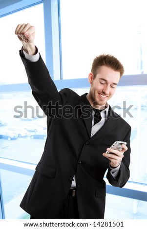 A shot of a happy caucasian businessman raising his arms in happiness after receiving a text message