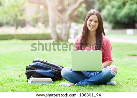A shot of a hispanic college student sitting on the grass working on laptop at campus - stock photo