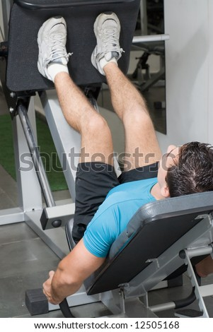 A shot of a male weightlifter doing leg presses. - stock photo