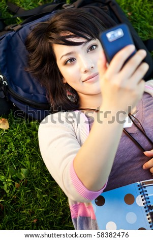 A shot of a mixed race girl texting on the phone at campus
