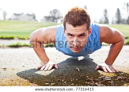 A shot of a mixed race man doing push up outdoor