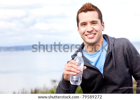 A shot of a mixed race man holding water bottle outdoor