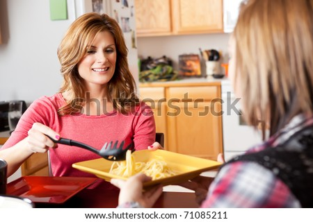 A shot of a mother serving food to her daughter - stock photo
