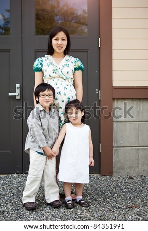 A shot of a pregnant Asian mother with her two kids outdoor - stock photo