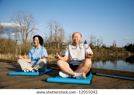 A shot of a senior asian couple practicing yoga and meditating