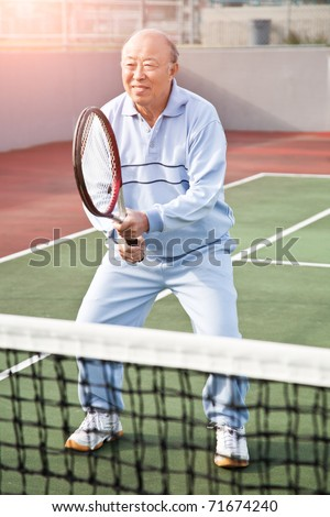 A shot of a senior asian man playing tennis - stock photo