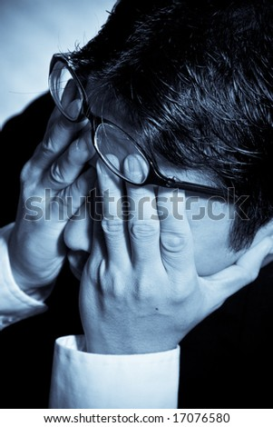 A shot of a stressed businessman in blue tone