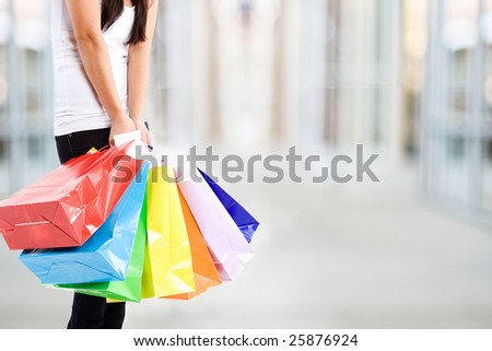 A shot of a woman carrying shopping bags at a mall - stock photo