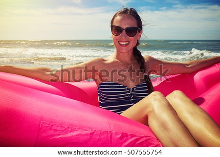 A shot of a woman wearing brown sunglasses and a striped swimming suit sitting on the pink airboat on the beach on a sunny day. The skinny female whose brown hair is tying into braid is smiling