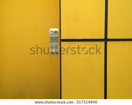 A shot of a yellow door with yellow wall.