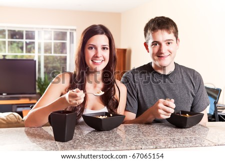 A shot of a young couple eating breakfast