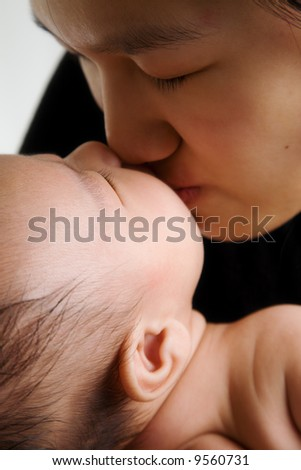 A shot of an asian mother kissing her cute baby boy