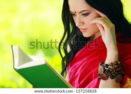 A shot of an asian or indian student in traditional clothes studying on campus park - stock photo