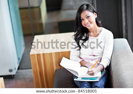 A shot of an Asian student studying on campus
