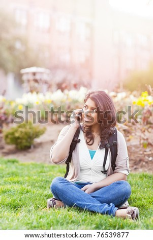 A shot of an asian student talking on the phone on campus - stock photo