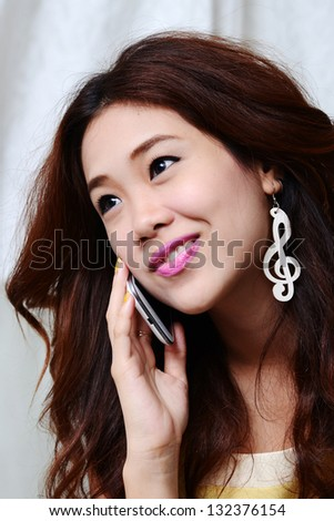 A shot of an asian woman talking on the phone - stock photo