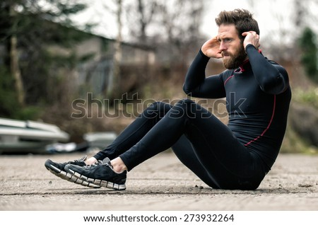 A shot of an athlete doing sit-ups outside - stock photo