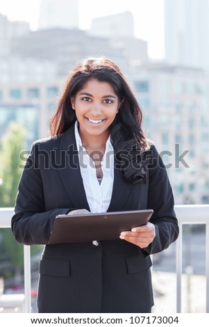A shot of an Indian businesswoman holding a tablet PC outdoor - stock photo