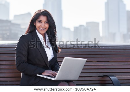 A shot of an Indian businesswoman working on her laptop outdoor
