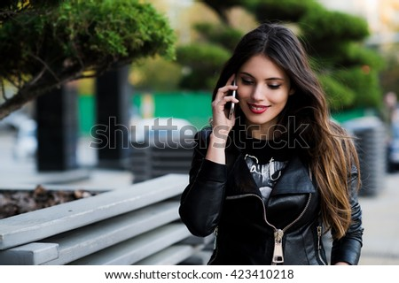 A shot of an student talking on the phone outdoors - stock photo