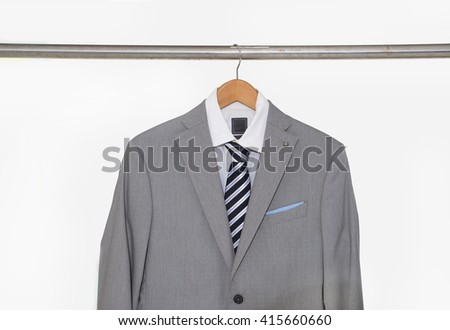 A shot of business man gray suit clothes hanging - stock photo