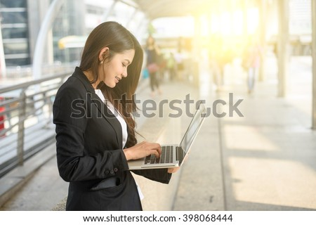 A shot of businesswoman working on her laptop outdoor - stock photo