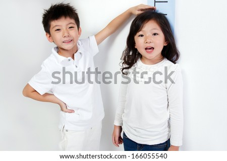 A shot of Girl measuring height - stock photo