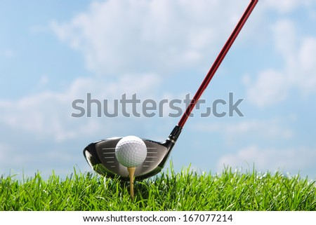 A shot of Golf club teeing up to hit ball - stock photo