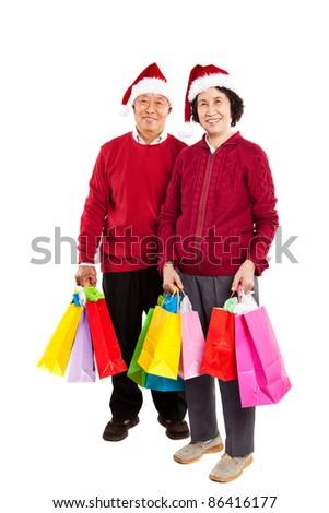 A shot of senior Asian couple carrying shopping bags celebrating Christmas - stock photo