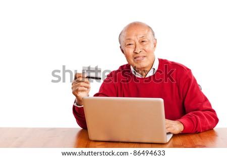 A shot of senior Asian man shopping online celebrating Christmas - stock photo