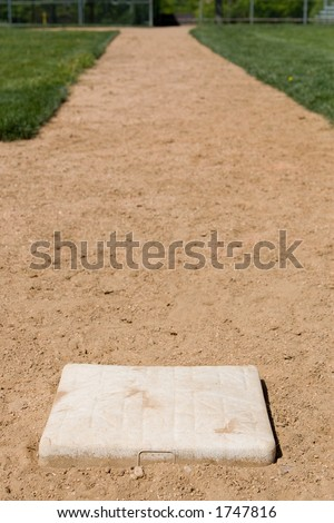 A shot of the baseball diamond base path between third and home, with third base in sharp focus and the area with home out of focus to emphasis the distance to home plate. - stock photo