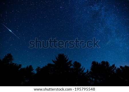 A shot of the milky way and an Iridium flare in the night sky in the Blue Ridge Mountains of North Carolina - stock photo