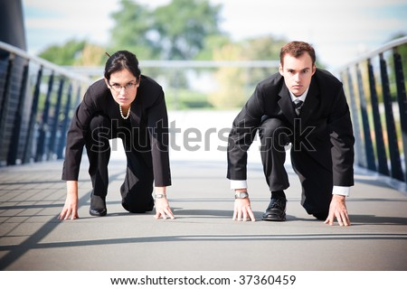A shot of two business people in a running start position competing against each other