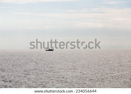 A shrimp boat pulling a net in sillouette - stock photo