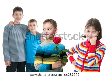 A shy kid attempts to present a red rose to a pretty girl; his two friends are smiling; isolated on the white background
