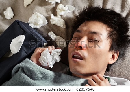 A sick male sleeping with lots of used tissue around him - stock photo
