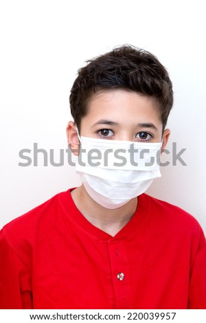 A sick young boy with face mask on.