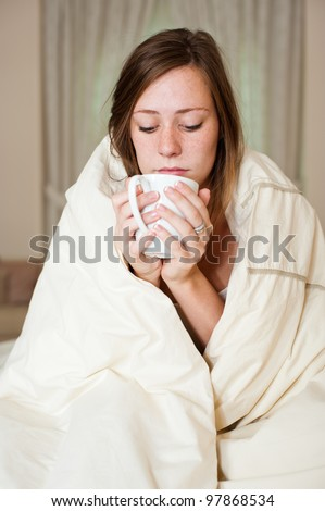 A sick young lady in bed, sitting with a blanket over her shoulders and a cup of hot beverage. - stock photo