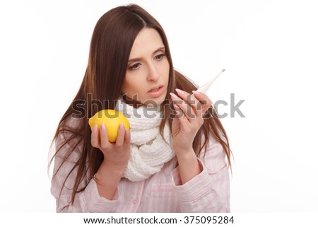 A sick young woman looking at the thermometer and holding a lemon
