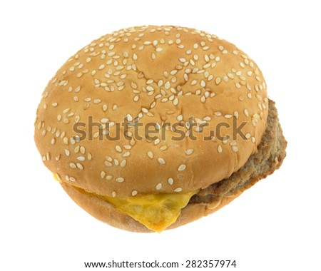 A side angle view of a prepared frozen cheeseburger in a sesame seed bun.