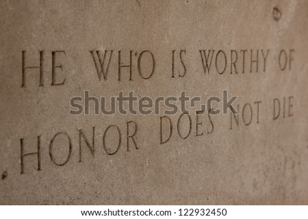 A side angled, close up view of the phrase 'He Who Is Worthy Of Honor Does Not Die' etched in stone. - stock photo